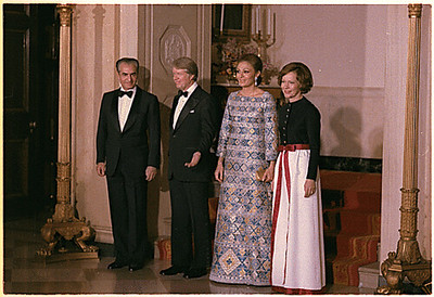President Jimmy Carter and his wife Rosalyn pose for a photograph with the Iranian Shah, Mohammed Reza Pahlavi and his wife, Farah Pahlavi dressed in tuxedos and evening gowns