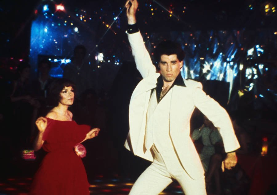 an iconic image from the film Saturday Night Fever with John Travolta in his white leisure suit doing the Point Move on the disco floor