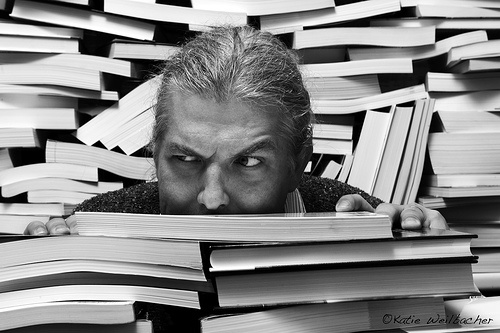 man hiding in piles of books