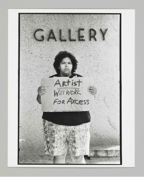 """b&w photo of artist holding sign in front of gallery that says """"will work for axcess"""""""
