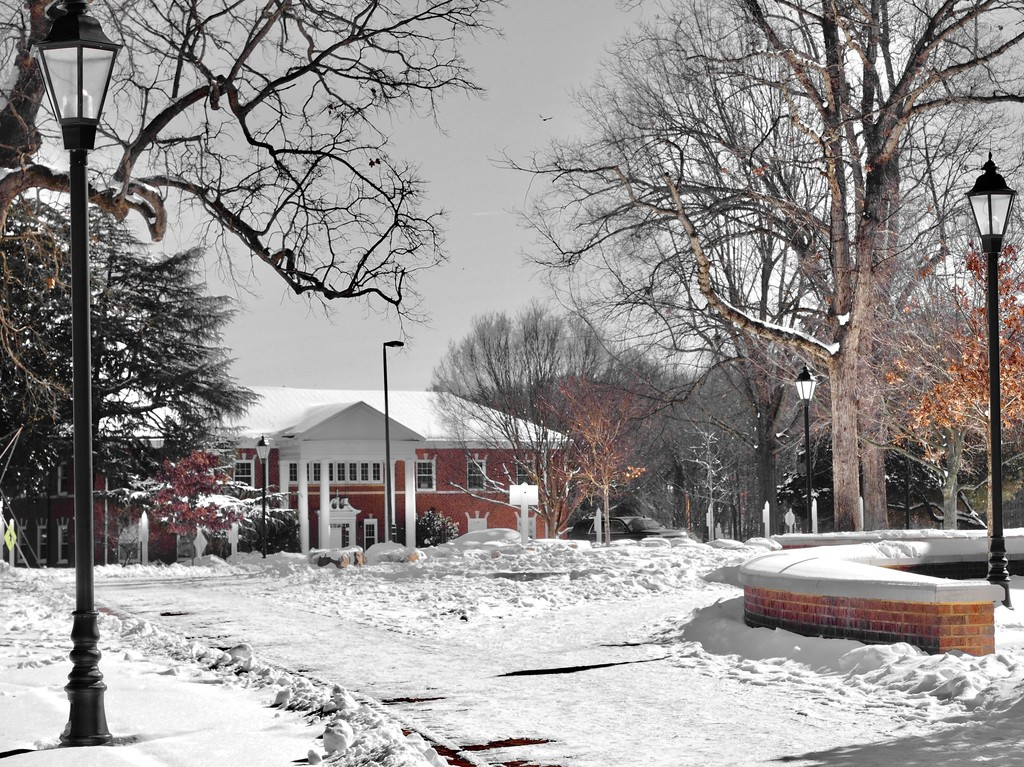 Guilford College in the snow: photograph of a snowy path leading to a brick building, with lamps and trees on either side