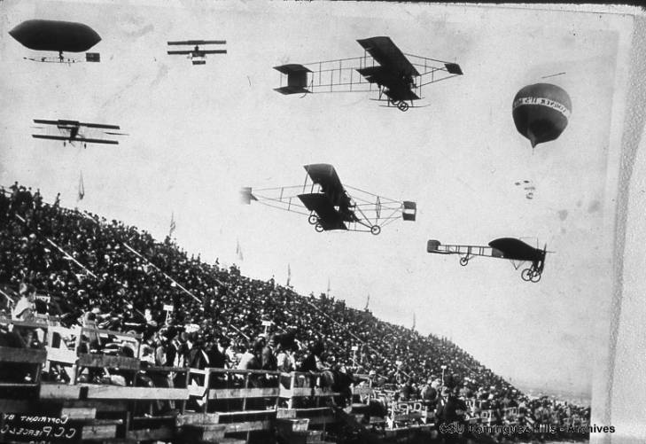 Image of planes, balloons, and dirigibles in flight over the grandstand