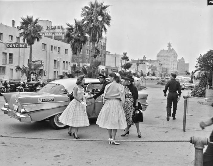 Image of women in dresses in front of car during a Miss Universe contest.