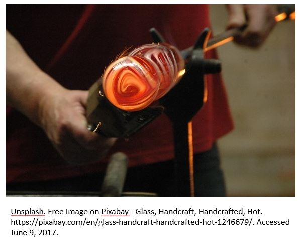 A zoomed in photo showing just the man's hands shows a man forming a piece of hot glass into a shape.
