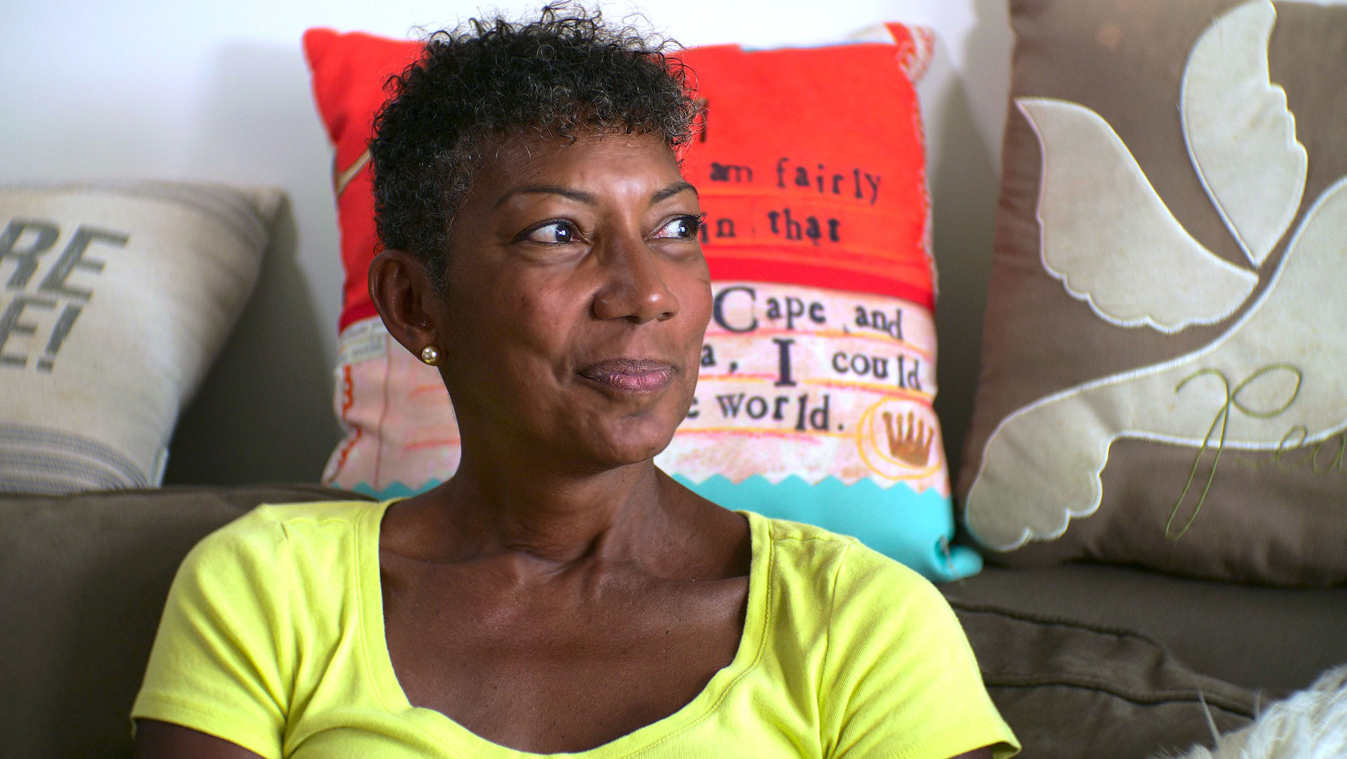 A Black woman in a yellow tshirt sits in front of a colorful pillow looking to the right.