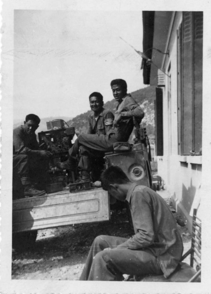 Nisei solders on military vehicle