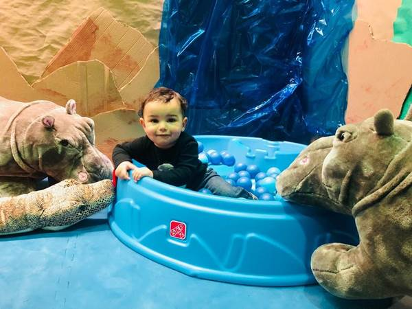 Jungle with child in wading pool with stuffed hippos