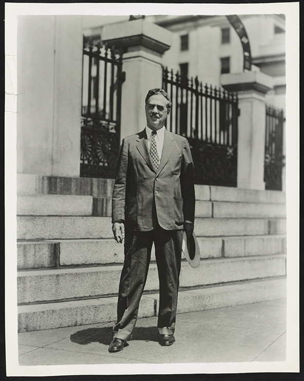 Photograph shows Henry Alsberg, director of the Federal Writers' Project from 1935 to 1939, standing on a city sidewalk.