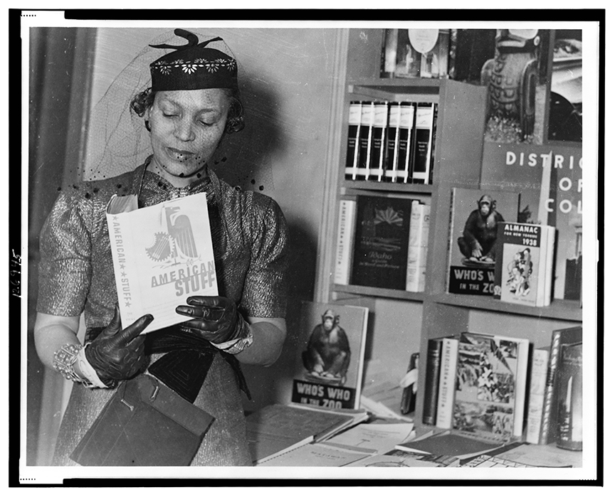 Zora Neale Hurston, half-length portrait, standing, facing front, looking at book, American Stuff, at New York Times Book Fair