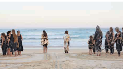 A group of people stand on sand on the shore of an ocean