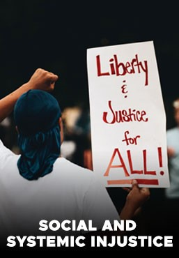 protestor holding sign that reads liberty and justice for all