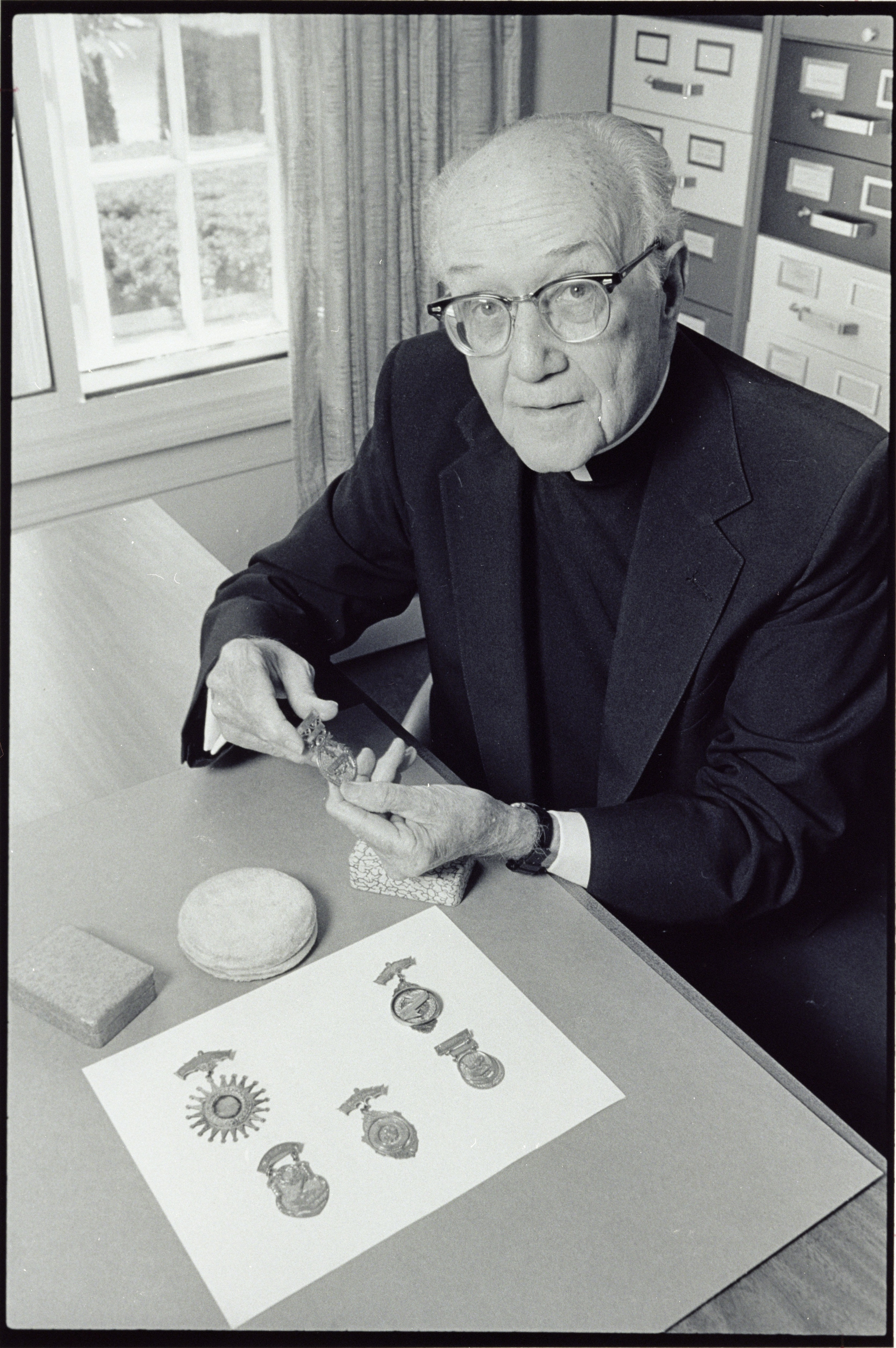 Image of University Historian Charles F. Donovan, SJ, sitting at desk displaying six medals awarded to David Regan, Class of 1894