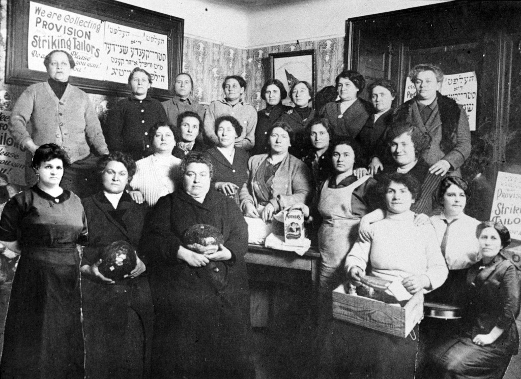 Women posed in a shop with food & posters