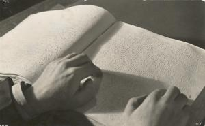 Hand of a white man reading braille book