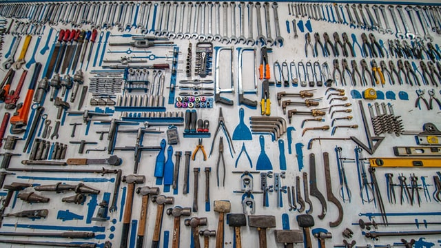 Hand tools (wrences, saws, hammers, etc.) hanging on a wall