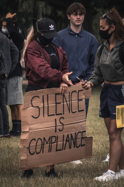 """Protesters with a cardboard sign """"silence is compliance"""""""