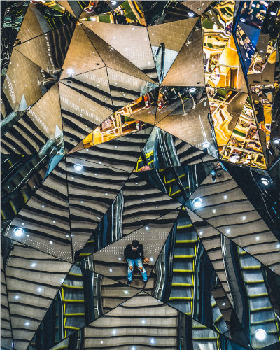 abstract photograph with reflective triangles of urban environment (stairs, concrete, individual sitting alone)