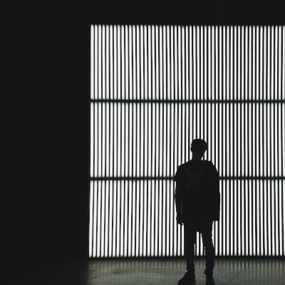 silhouette of young person standing in front of window with blinds
