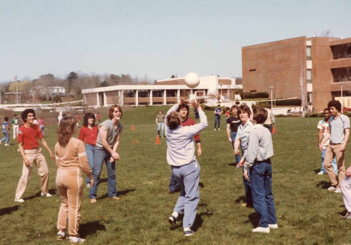 NECC students in plain clothes playing volleyball.