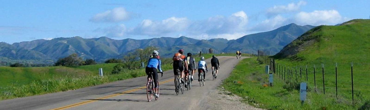Cycling group in Central California with mountains in the distance.