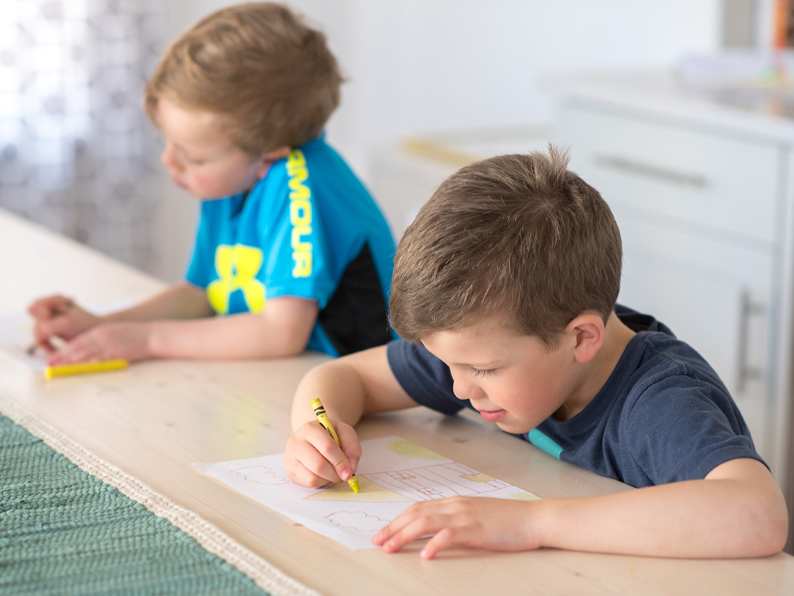 Two young boys coloring pictures at a table