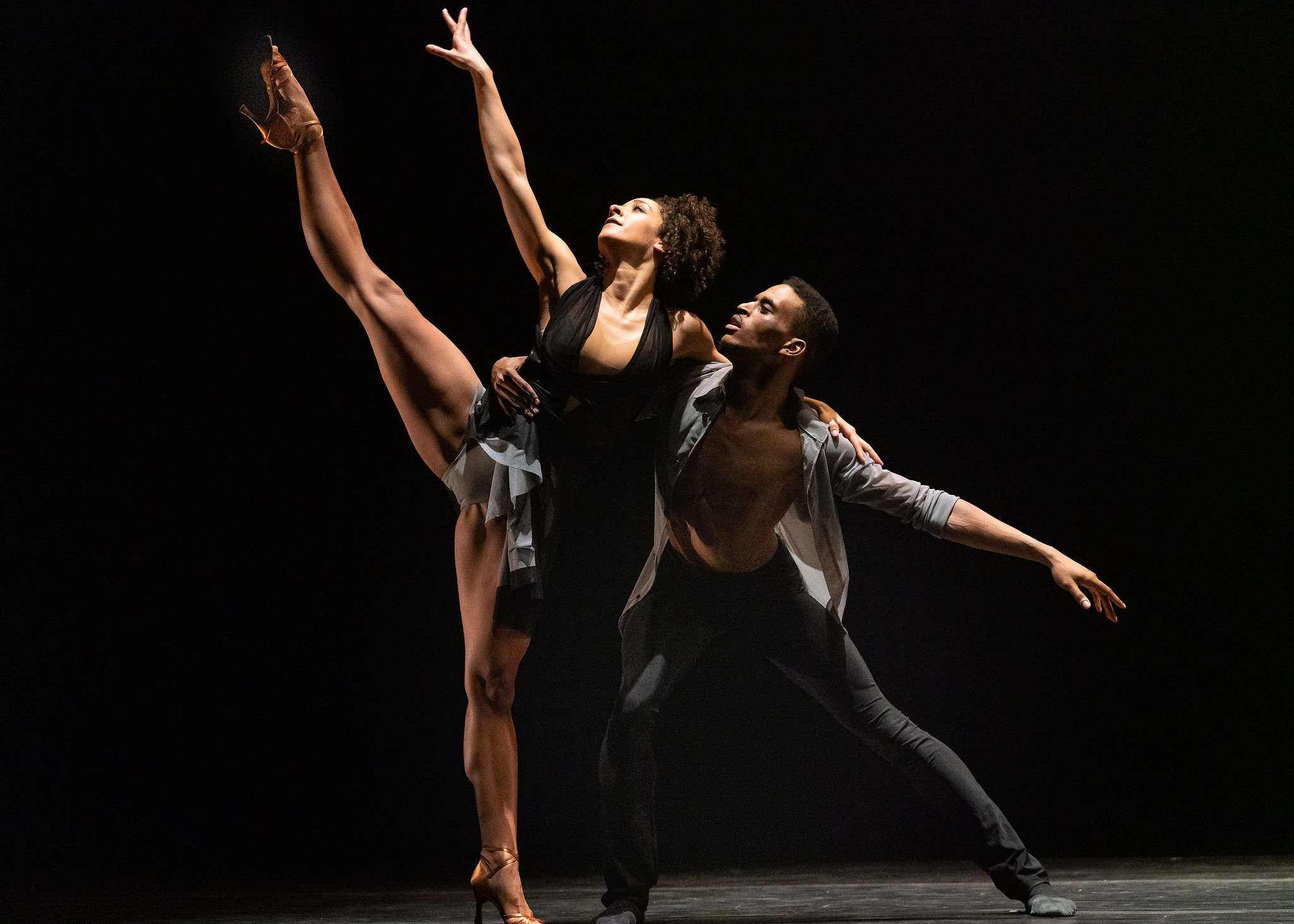 A woman and a man performing a dance routine against a black background