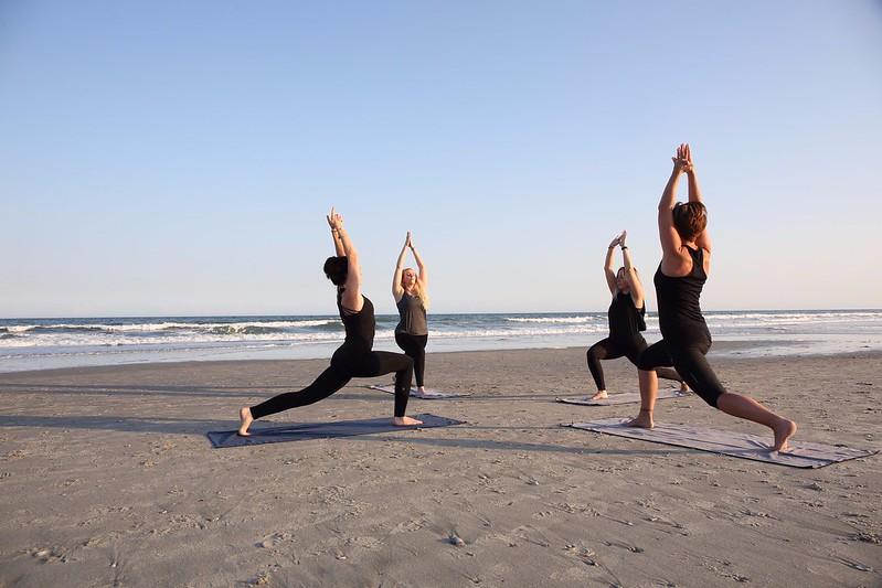 A group of four people doing yoga on a beach