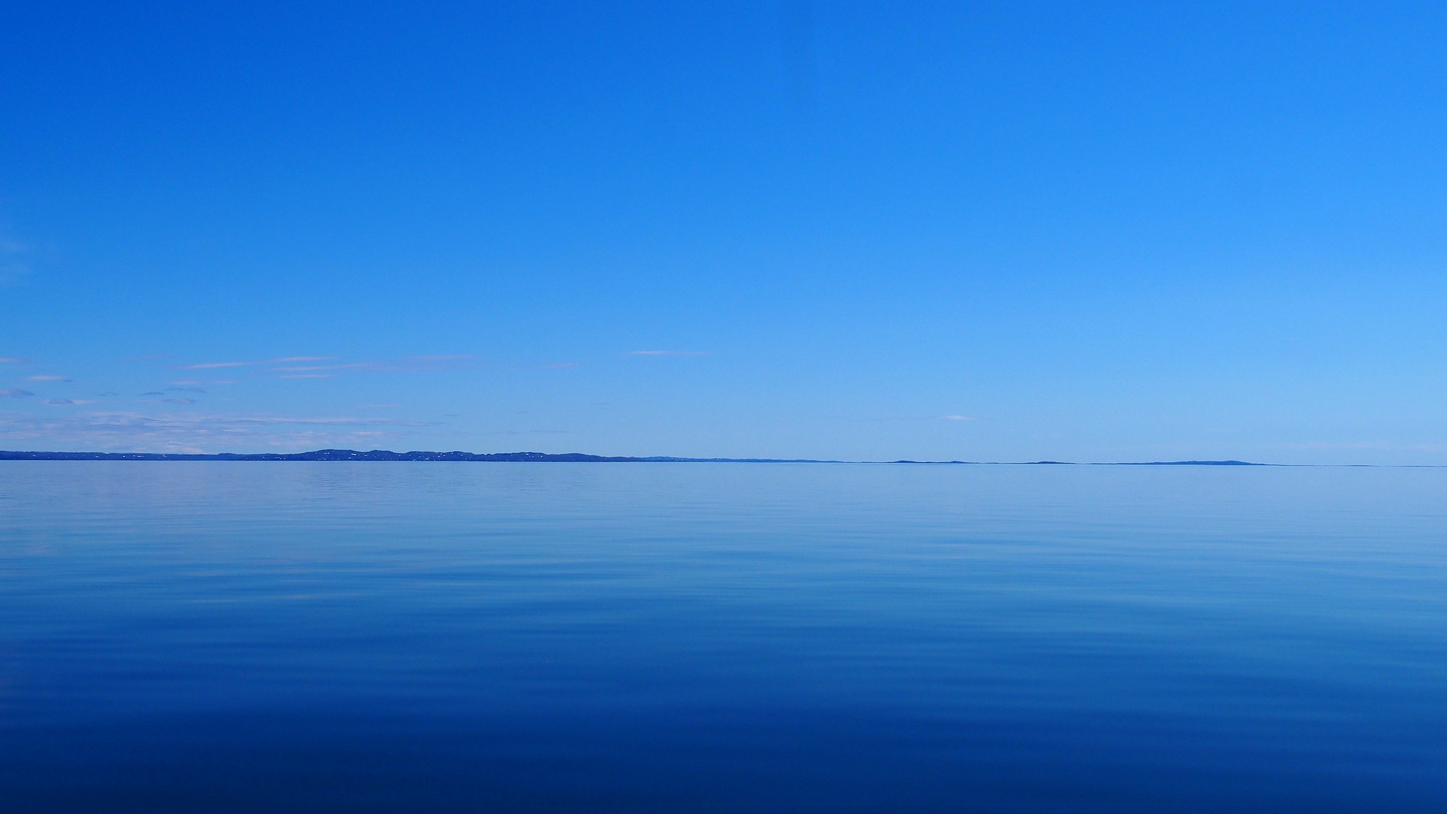 A calm, blue view of the horizon reflected over a body of water