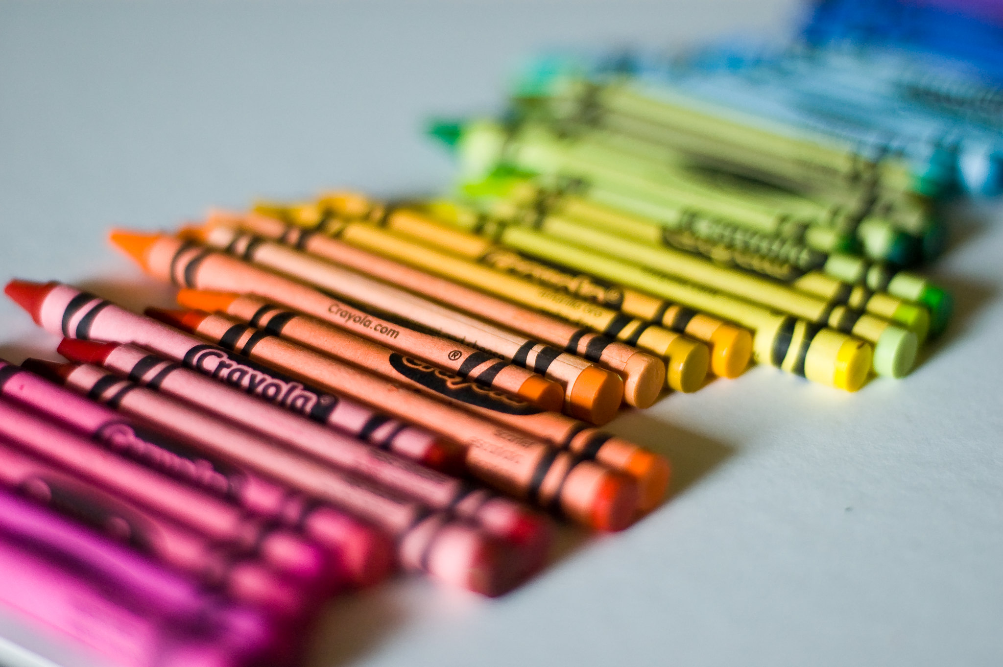 Crayons arranged on a table in rainbow order