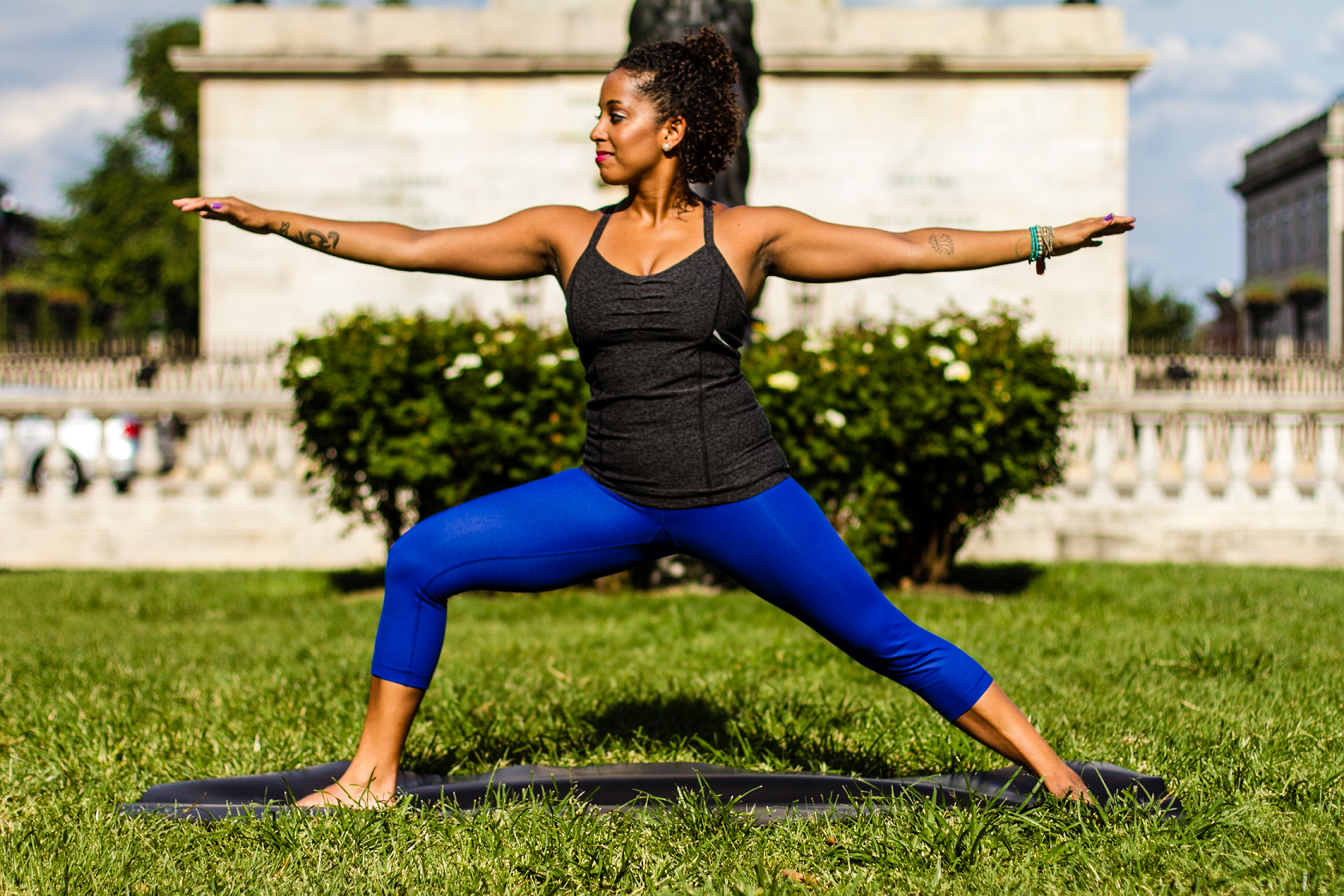 A woman in warrior two pose on a yoga mat outside