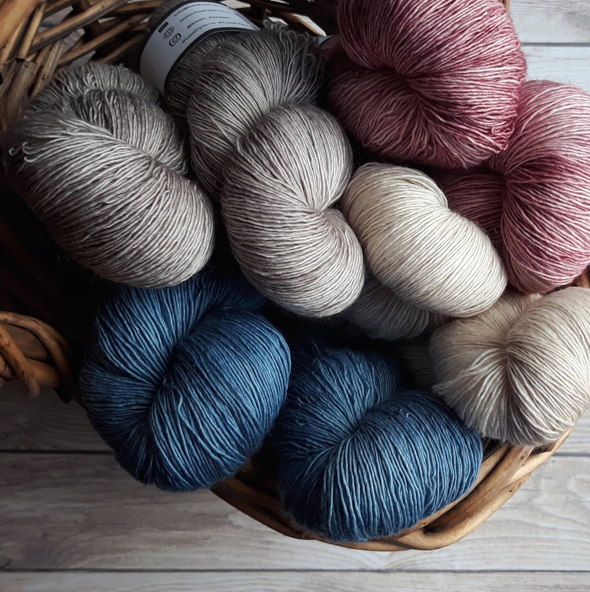 Skeins of yarn in shades of white, gray, red and blue in a brown basket
