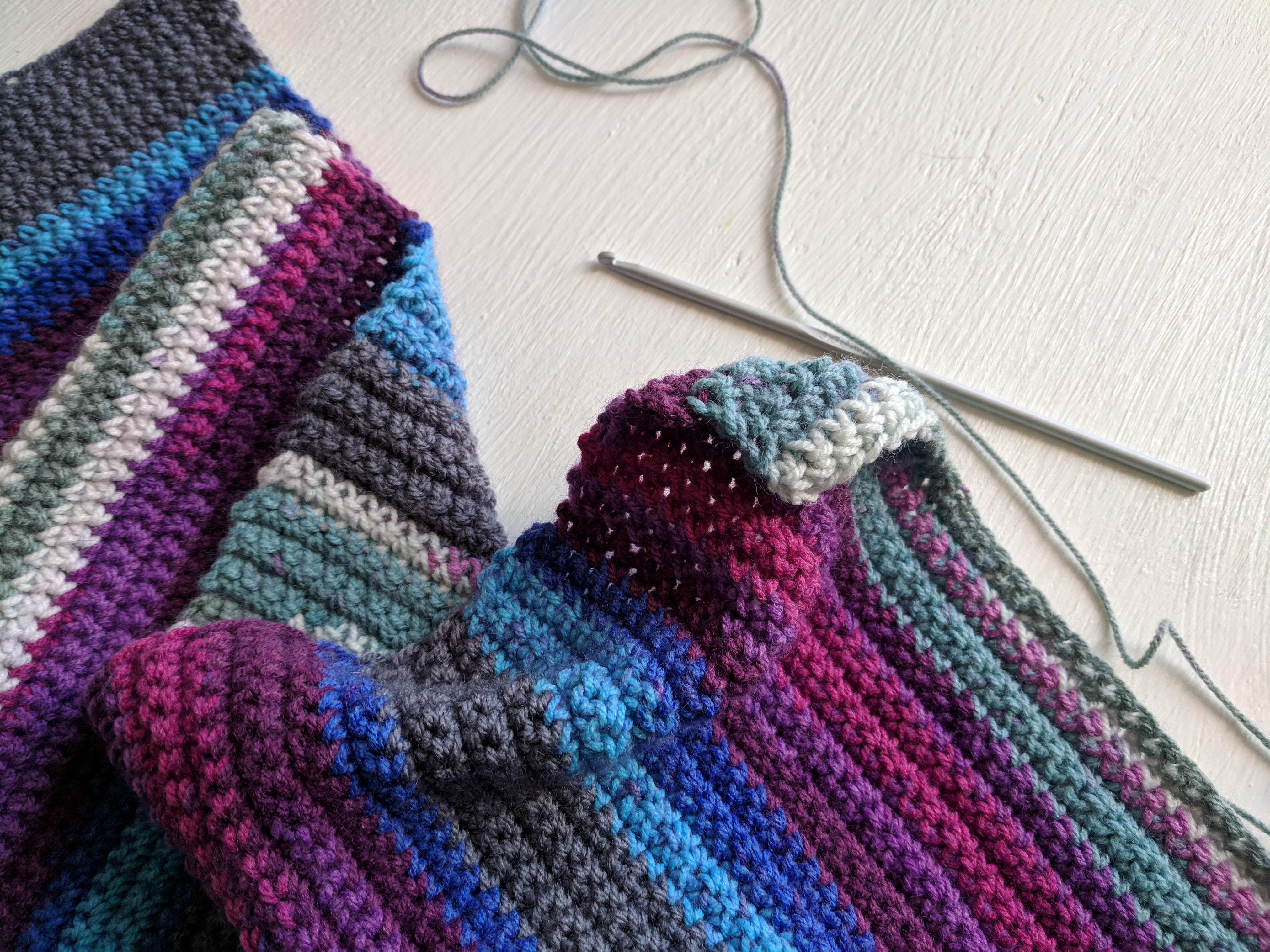 A striped crocheted blanket with crochet hook and string