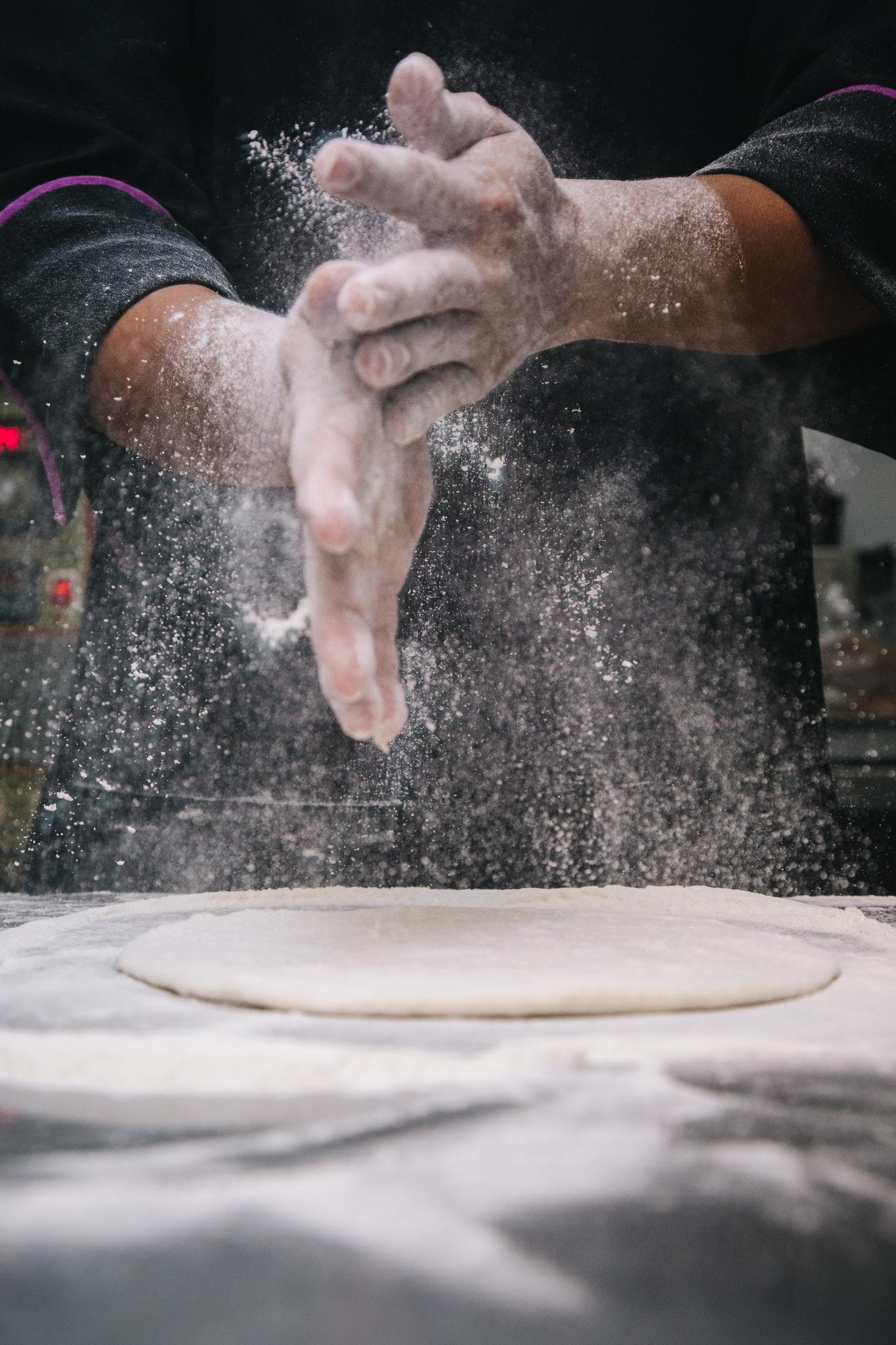 Baker's hands brushing off flour over bread dough