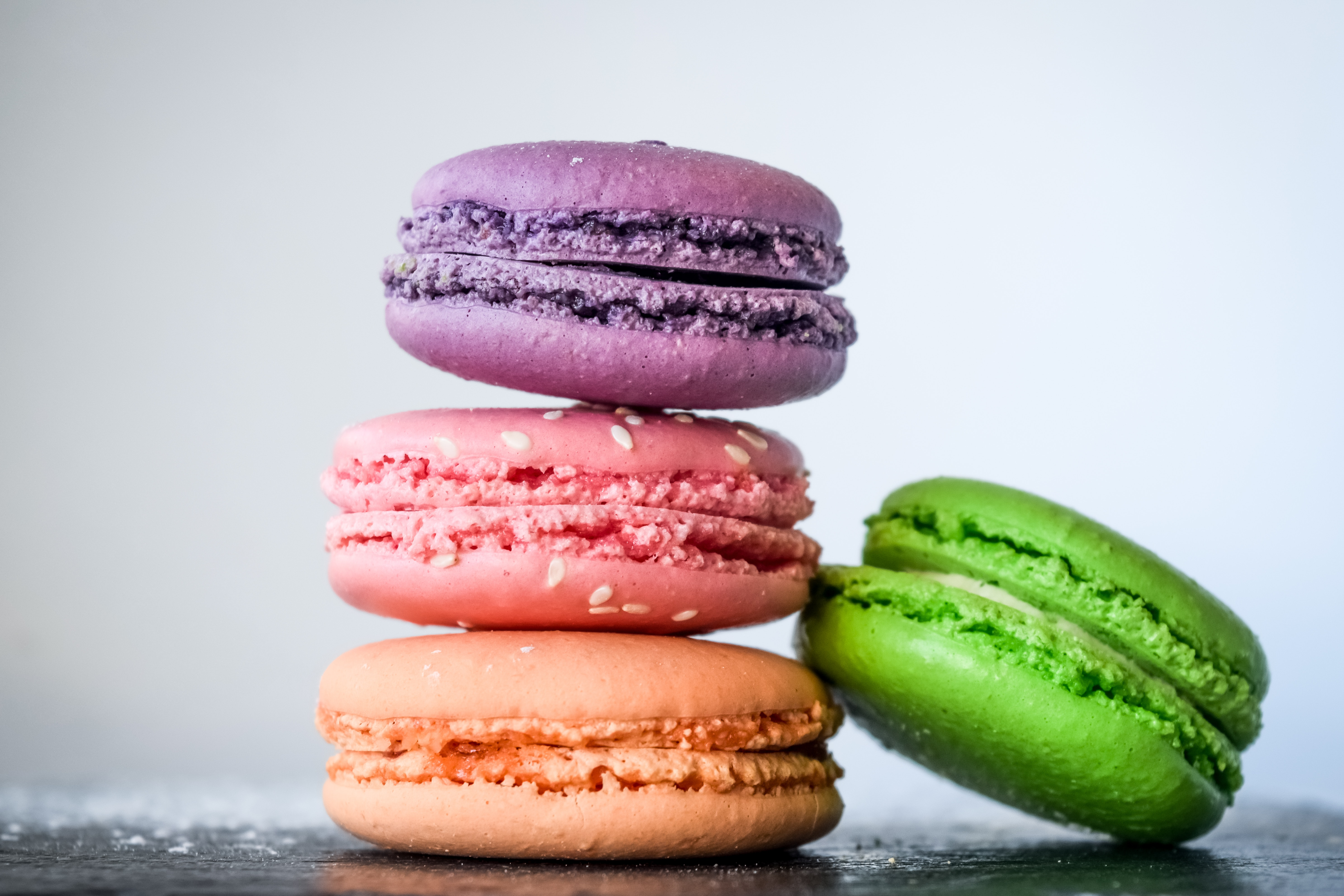 Four macarons in purple, pink, orange and green stacked on a table
