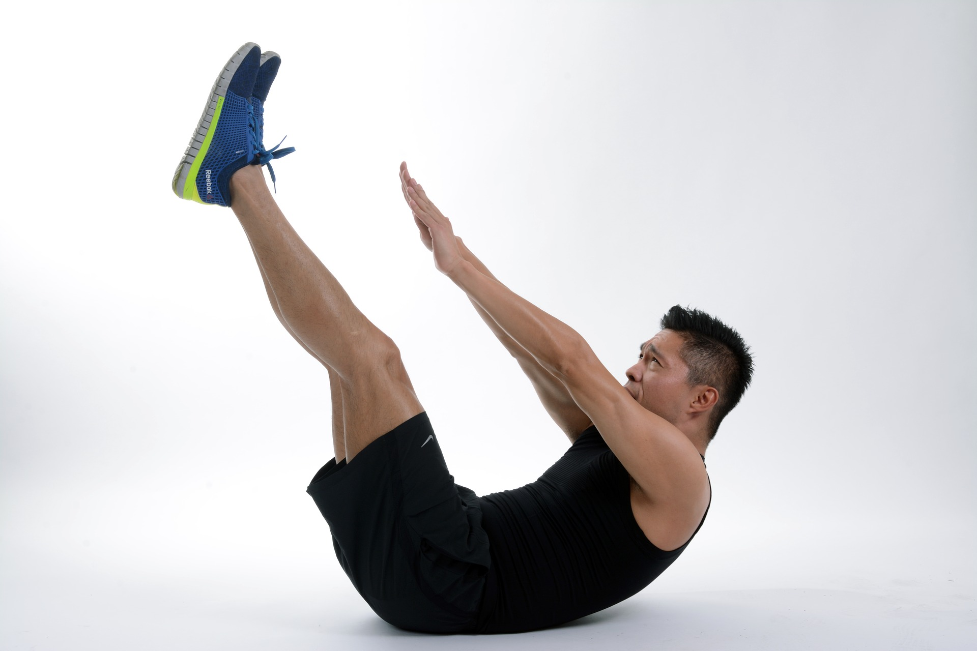 Man exercising with his legs raised while on his back reaching towards his feet with both hands