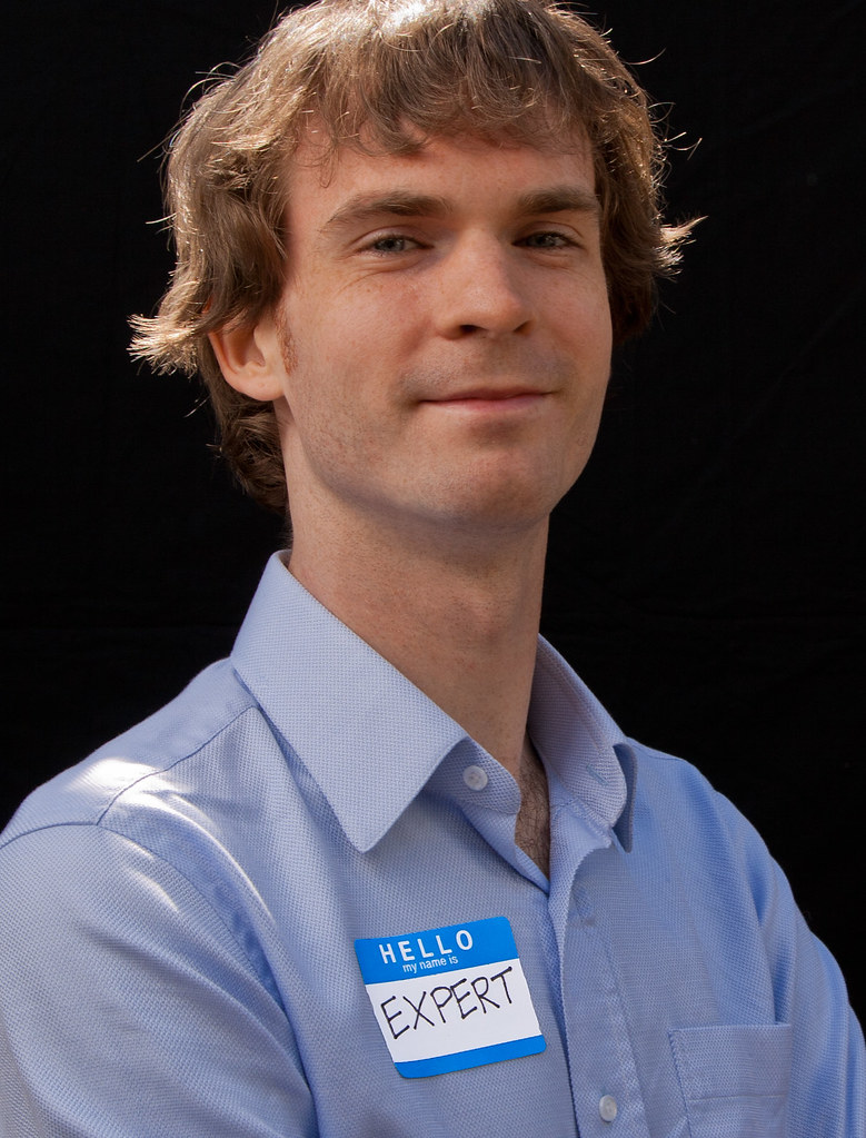 A photograph of a Caucasian man with a name tag that says expert.