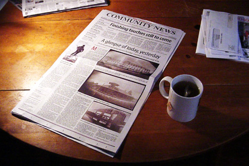 A photograph of an open newspaper on a wooden table next to a hot cup of tea