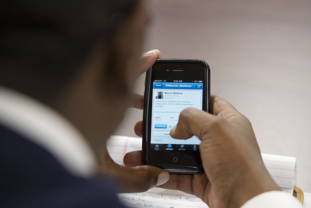 A photograph of a person using their phone to write and send a tweet.