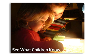 Photo of two children looking at materials on a desk