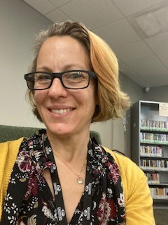 Librarian Rachel Peterson with short blonde hair and dark-rimmed eyeglasses, wearing a flowered dress and a yellow cardigan.