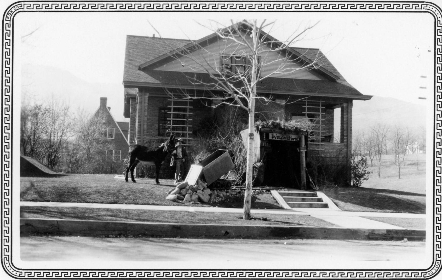 Student with burro, at decorated fraternity house, Homecoming 1928