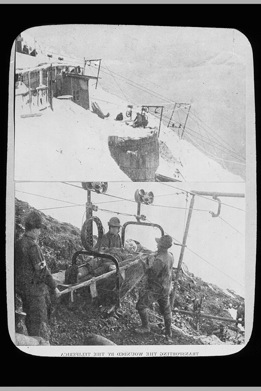 Soldiers loading wounded man on ropeway carrier, snowy Dolomite mountains