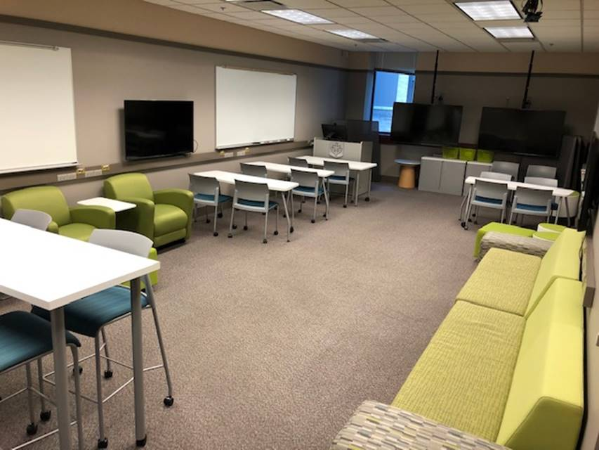 Photo of tabes and monitors in the Loop Library Collaboratory.