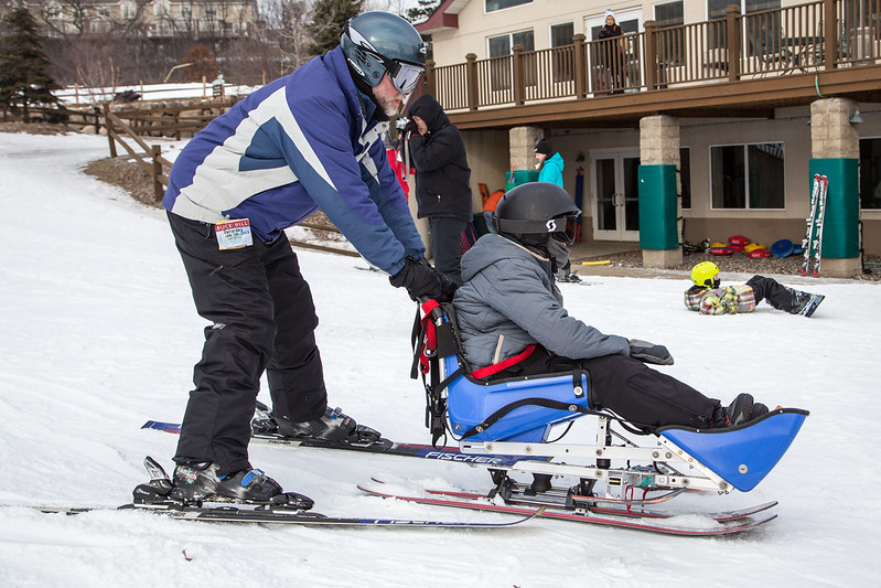 skier using wheelchair skis with a guide