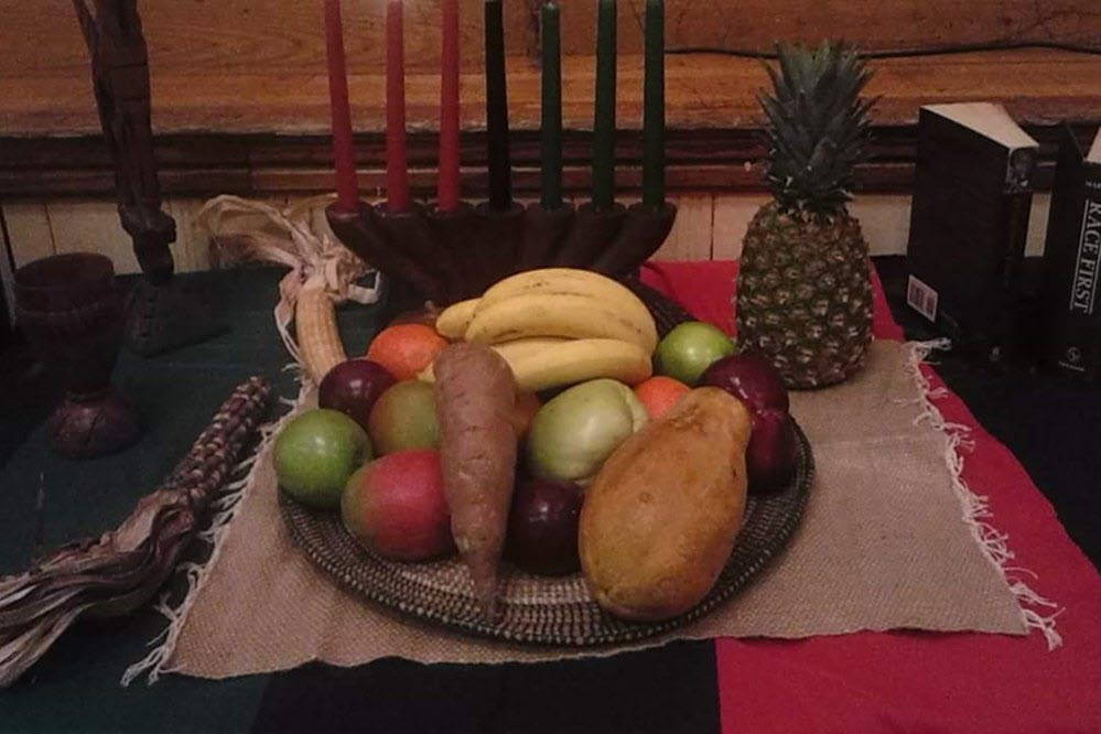 fruits and vegetables on a woven tray; tray sits on a table with books, candles, and a goblet