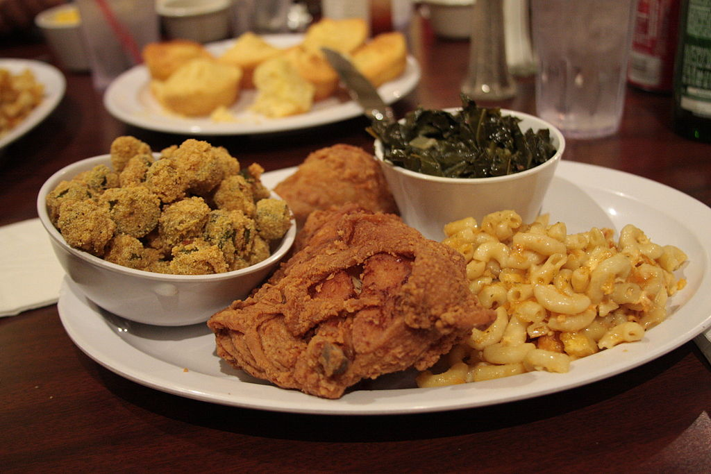 photo of a dinner plate with fried chicken, okra, collard greens, and mac n cheese
