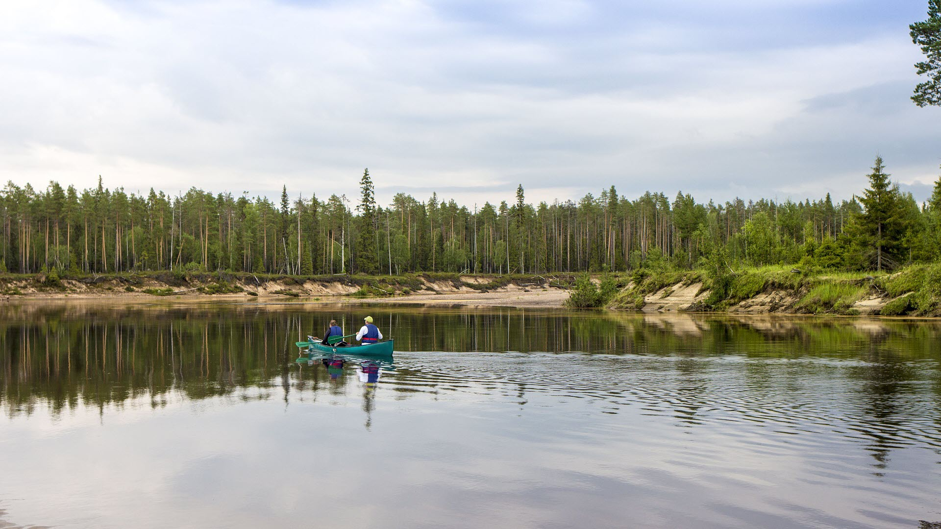two men fishing on a boat on a lake; trees can be seen on the shoreline