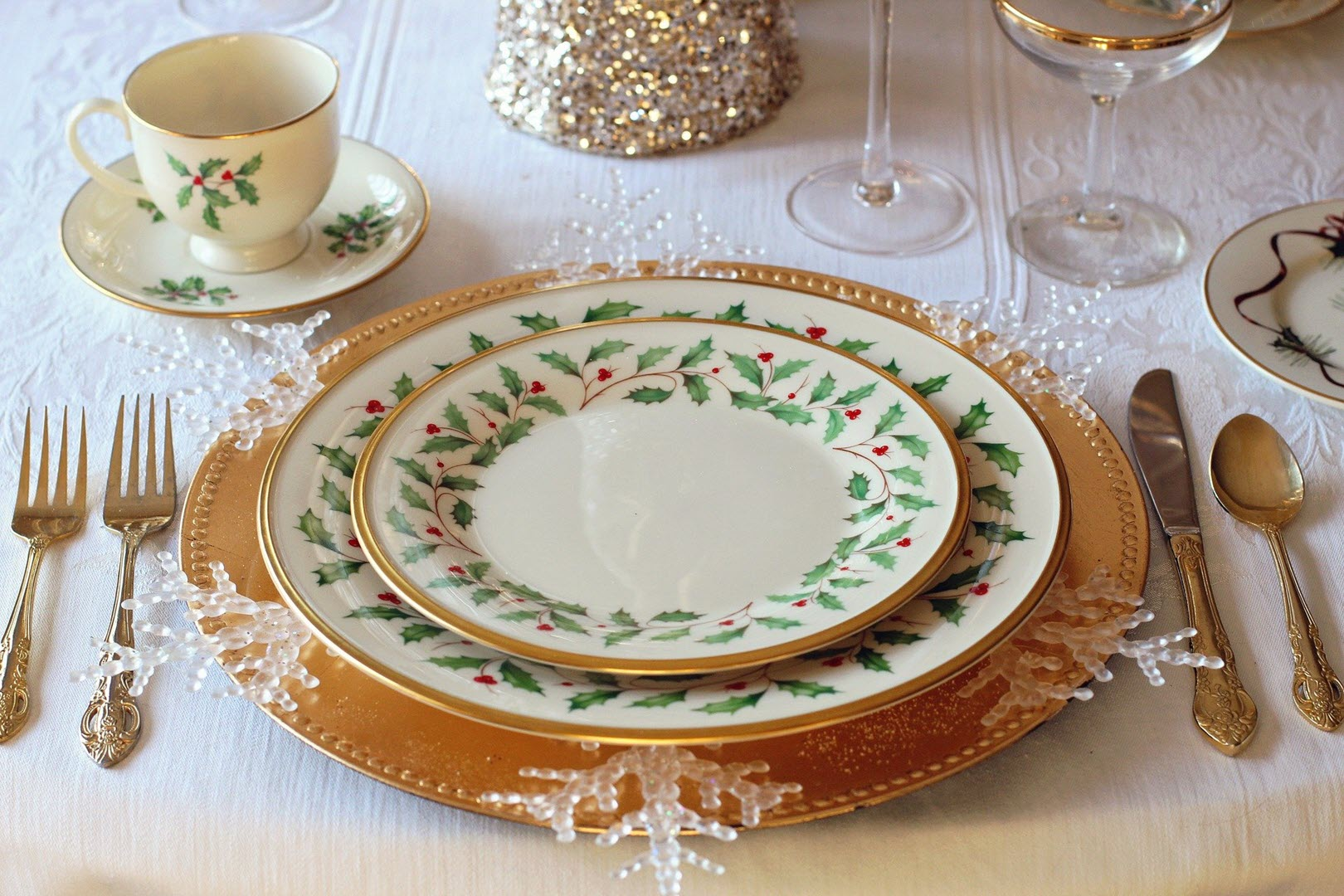 Dinner table setting, plates, glasses, and cutlery, decorated with snowflakes and holly leaves