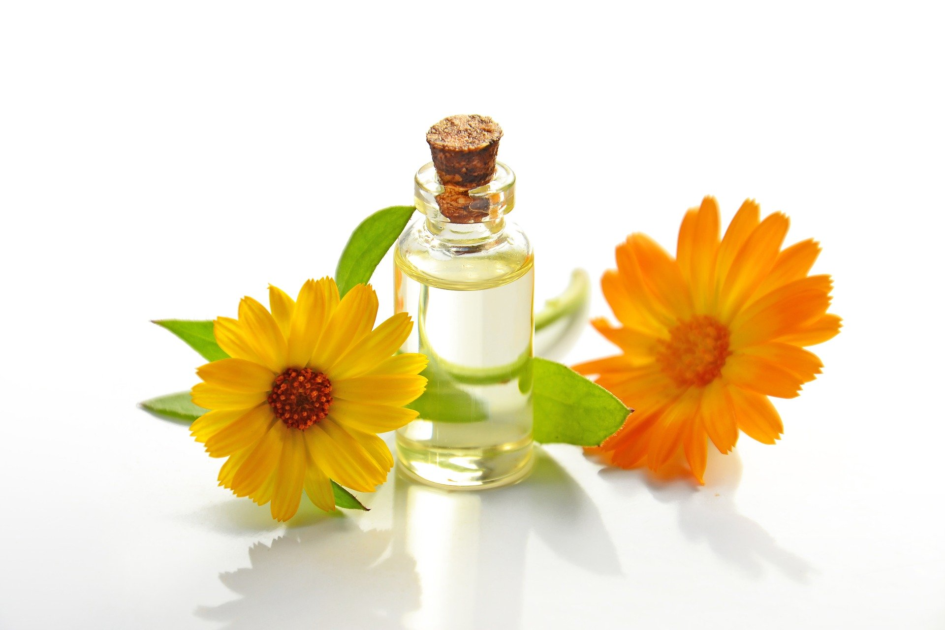 essential oils in a vial with two flowers
