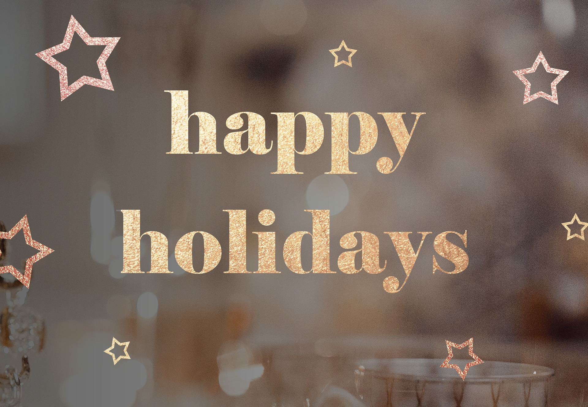 "text reads ""happy holidays"" on a golden background with small stars"